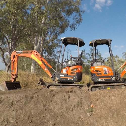 Two Mini Excavator standing back to back