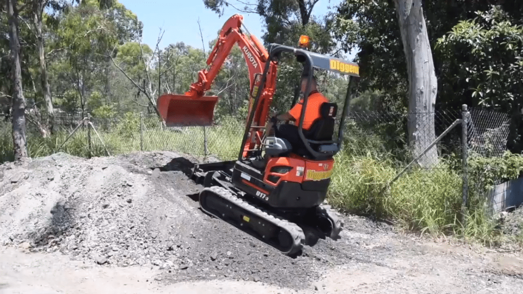 Preparing to climb a slope with a mini excavator